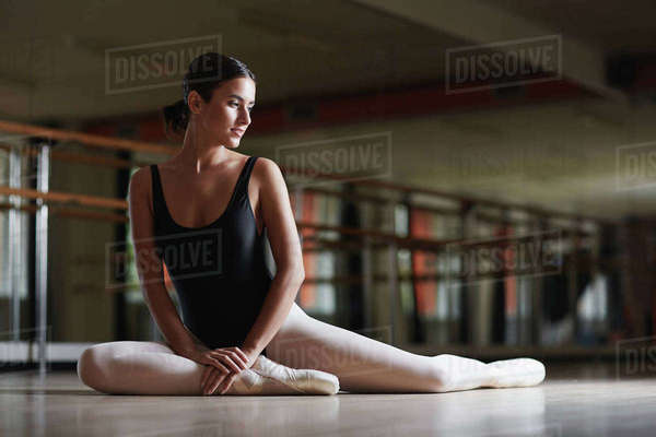 Cute young woman in ballet clothing sitting on the floor of class Royalty-free stock photo
