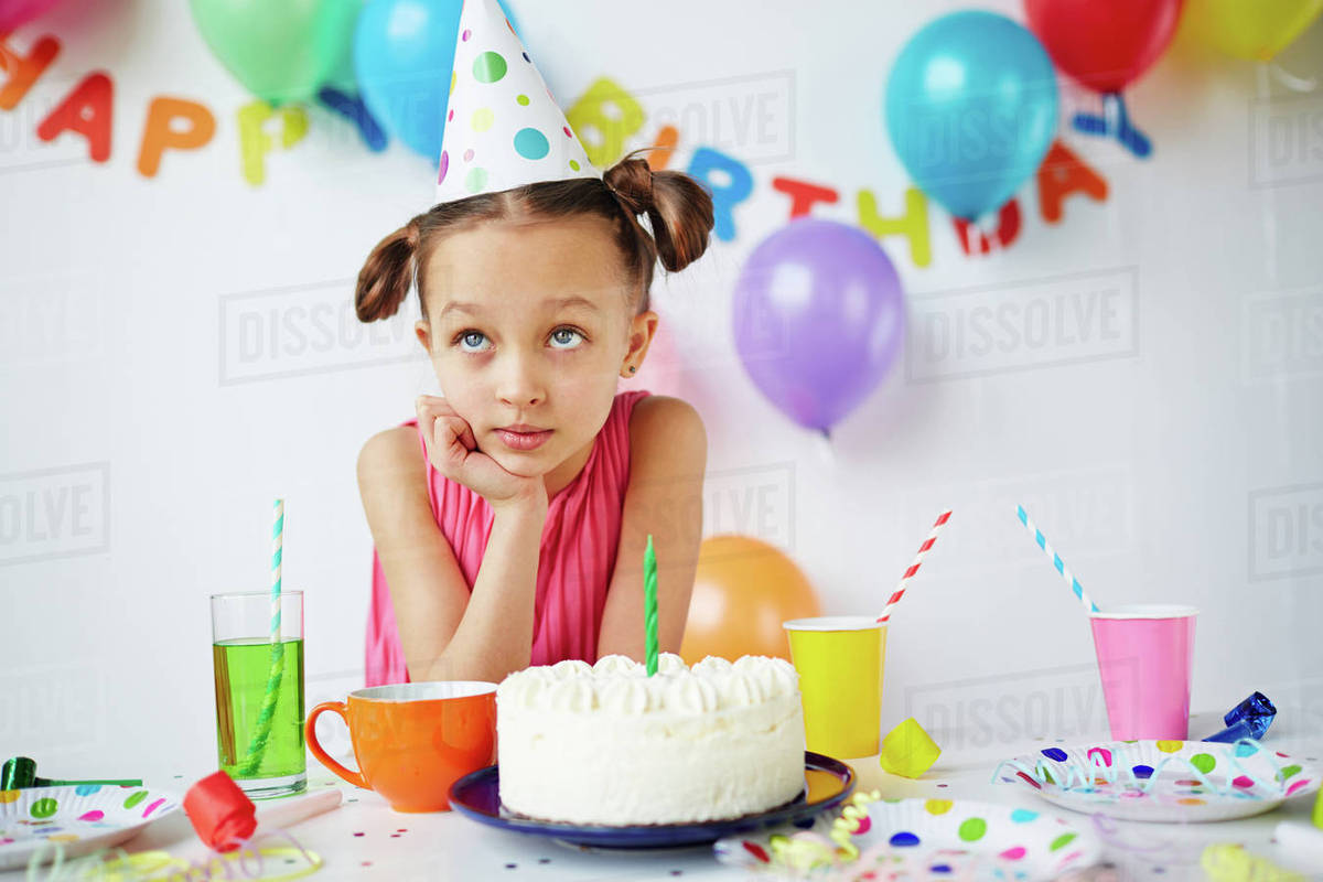 Cute Girl Making Wish By Birthday Cake Stock Photo Dissolve