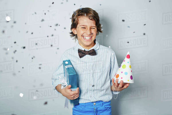 Cheerful boy holding birthday present and cap Royalty-free stock photo