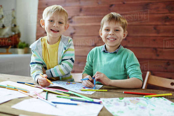 Adorable boys coloring pictures with highlighters at leisure Royalty-free stock photo