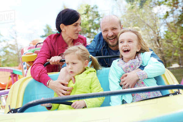 Ecstatic kids and parents spending leisure in amusement park Royalty-free stock photo