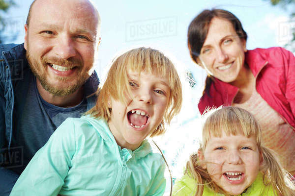 Cheerful man, woman and two little girls looking at camera outdoors Royalty-free stock photo