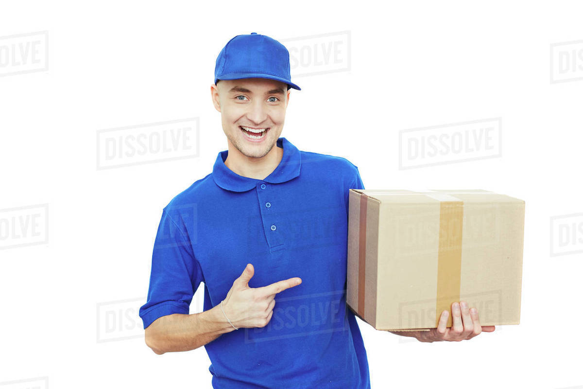 delivery man in blue uniform pointing at cardboard box stock photo
