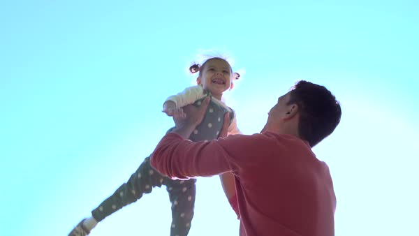 Slow motion of handsome father throwing his adorable daughter in the air Royalty-free stock video
