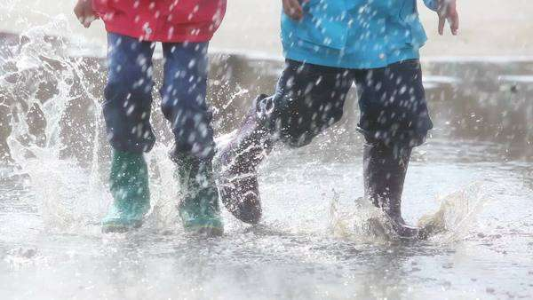 Boy and girl having fun on a rainy day jumping and dancing in puddle Royalty-free stock video