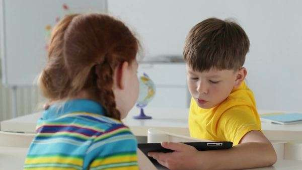 Boy using a digital tablet, girl watching him then turning and smiling at camera, shifting focus Royalty-free stock video