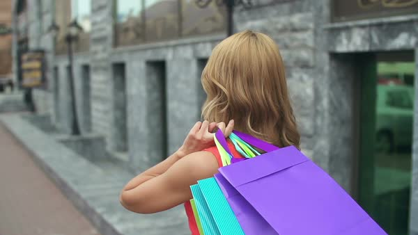 Camera following pretty girl strolling outdoors with shopping bags and turning to look straight at camera Royalty-free stock video