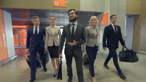 Business team of five approaching camera after arrival at the airport, team leader walking in front of other colleagues Royalty-free stock video