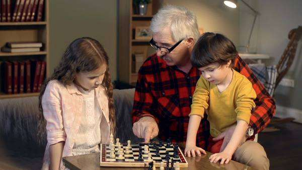 Little girl playing chess with her granddad trying to figure out her next move Royalty-free stock video