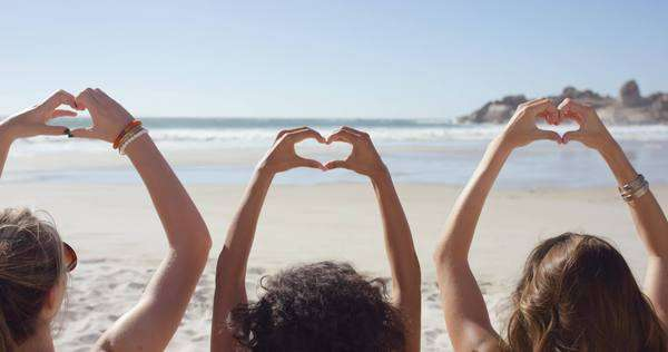 Group of friends on the beach making heart shaped gesture with their hands on summer vacation Royalty-free stock video