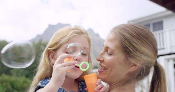 Mother and cute daughter blowing bubbles in the yard happy family home Royalty-free stock video