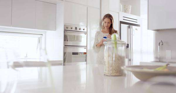 Woman eating natural yogurt in kitchen of white clean luxury home Royalty-free stock video