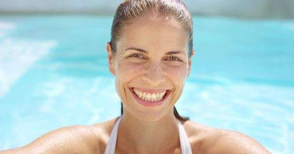 382ab076db9 Portrait of beautiful young woman smiling at edge of swimming pool with wet  hair Royalty-