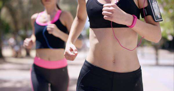 Close-up crop of torso two runner woman fitness athletic friends women jogging in the urban city Royalty-free stock video