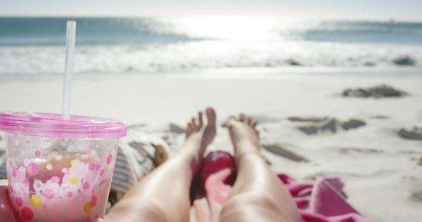 Pov of woman holding drink sexy legs on beach self shot Royalty-free stock video