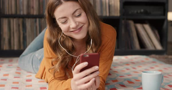 Beautiful smiling happy woman at home using touch screen smartphone listening to music in retro apartment vintage records in background orange retro colours and styling Royalty-free stock video