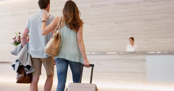 Attractive happy couple arriving at hotel reception lobby travelling on vacation checking in carrying luggage on honeymoon Royalty-free stock video