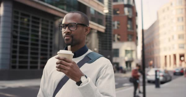 Businessman walking in city drinking coffee commuting independently between glass buidlings wearing glasses and smiling Royalty-free stock video