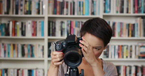 Attractive woman setting up digital camera on tripod at home using creativity and inspiration in front of colorful bookshelf Royalty-free stock video