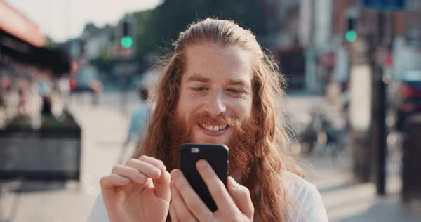 Portrait of happy hipster man with beard in city using smart phone sharing social media connection technology, slow motion Royalty-free stock video