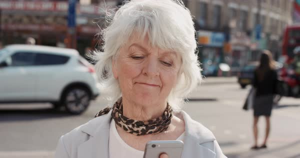 Portrait of happy mature old woman using smart phone in city, slow motion Royalty-free stock video