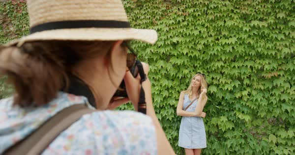 Professional photographer taking photo of model woman posing in front green wall of plants Royalty-free stock video