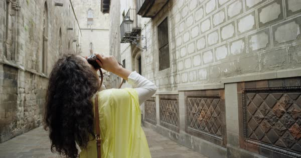 Woman taking photograph of Spanish wall architectural detail wearing cute summer dress Royalty-free stock video