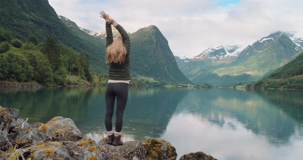 Woman with arms raised standing at edge of lake looking mountain view reflection Hike wearing green down jacket lifting arm up celebrating landscape enjoying vacation travel adventure Norway Royalty-free stock video