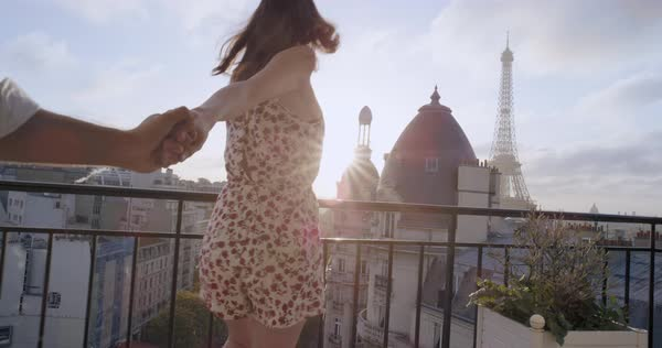 Young couple holding hands woman leading boyfriends walking towards sunrise hotel terrace view of Eiffel Tower Paris POV travel concept Royalty-free stock video