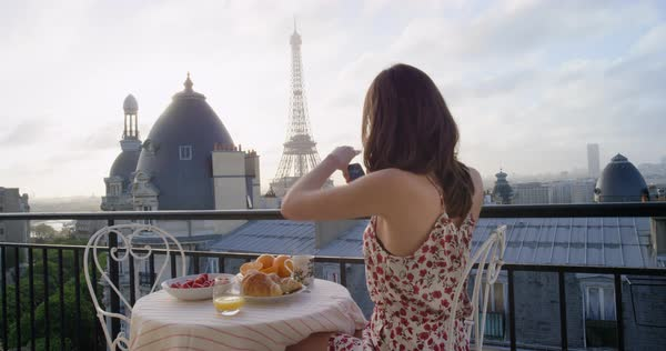 Woman taking photograph of Eiffel Tower Paris with smart phone sharing social media view from hotel terrace breakfast vacation Royalty-free stock video