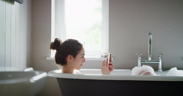 Woman relaxing in bubble bath lying in bathtub using smartphone browsing social media sharing photos Royalty-free stock video