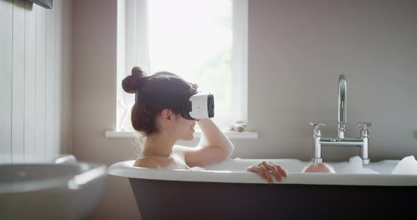 Young woman wearing virtual reality headset relaxing in bubble bath bathtub watching 360 video  Royalty-free stock video