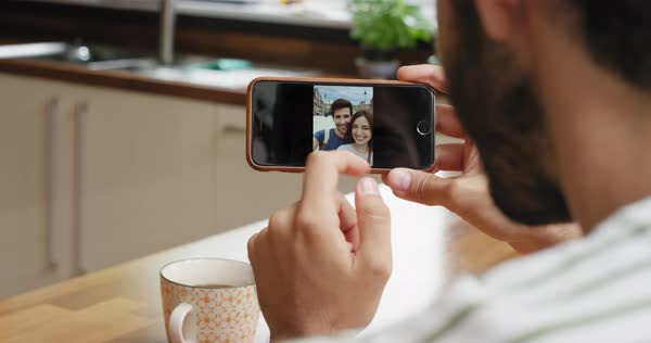 Close-up man using smartphone in kitchen scrolling travel photos  on touchscreen browsing social media Royalty-free stock video
