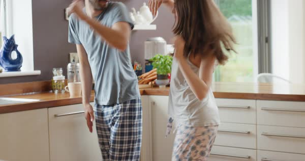 Young couple dancing in kitchen wearing pajamas listening to music morning at home Royalty-free stock video
