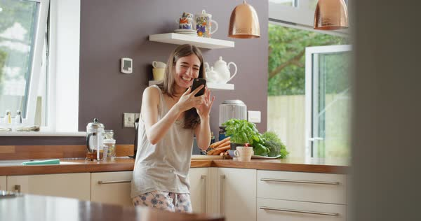 Young woman having video chat at home in kitchen holding smartphone  showing new home at webcam chatting to friend Royalty-free stock video