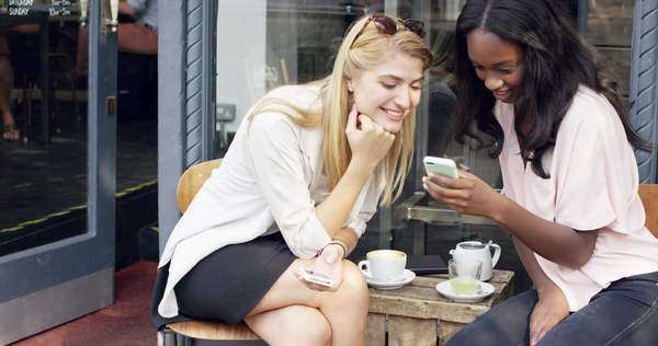 Female friends sharing together using smartphone in urban cafe Royalty-free stock video