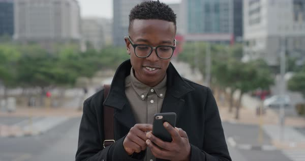 8db38c814731 Portrait young black man student using smartphone in city texting browsing  messages on mobile phone enjoying