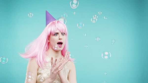 Crazy face pink hair woman dancing in bubble shower slow motion photo booth blue background Royalty-free stock video