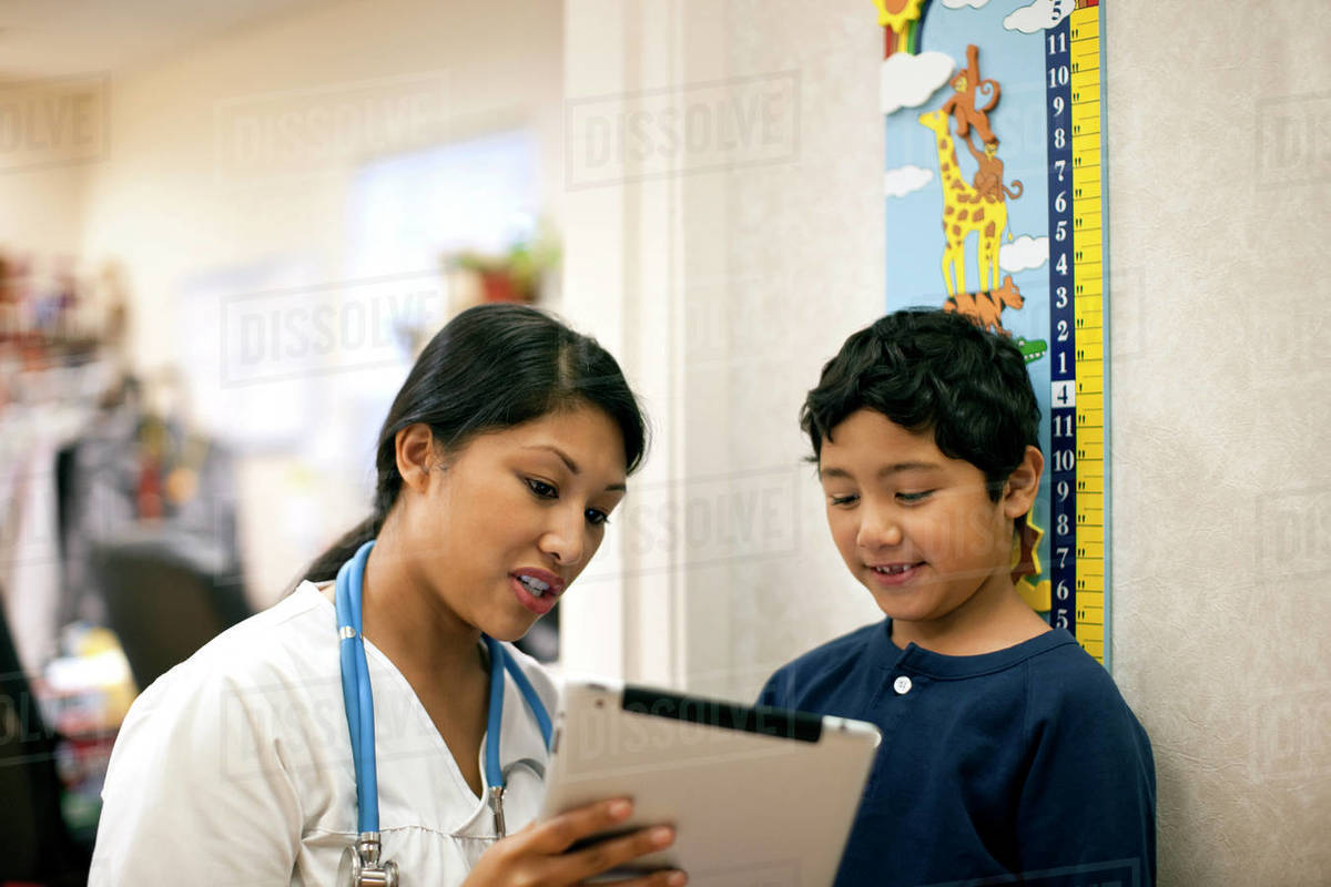 Nurse showing tablet to her young patient. Royalty-free stock photo