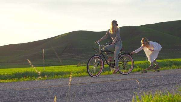 Two girls riding bike and skateboard down hill at sunset Royalty-free stock video