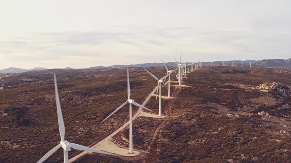 Aerial view wind turbines creating clean renewable energy in mountain landscape at sunset  Royalty-free stock video