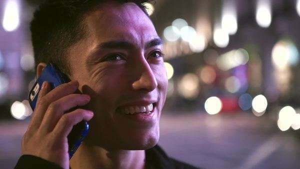 Handsome Asian man laughing as he talks on his phone in the city at night Royalty-free stock video