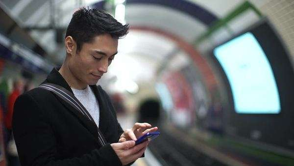 Young Asian man types on his phone as he waits for the subway train Royalty-free stock video