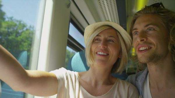 Attractive couple in love take a photo of themselves on a moving train Royalty-free stock video