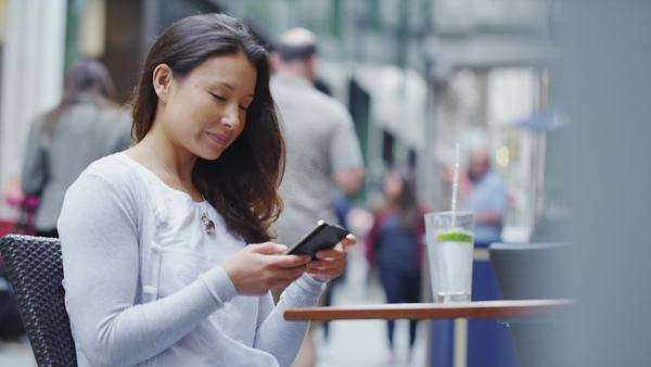 Attractive young woman at an outdoor table using her smart phone Royalty-free stock video