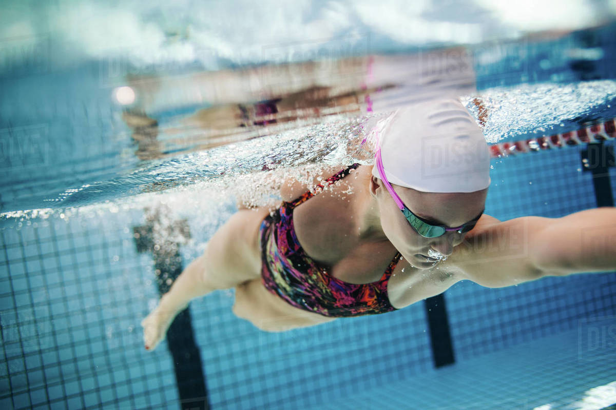 Underwater shot of young female swimmer swimming in pool. Fit young female  swimmer training in the pool. stock photo