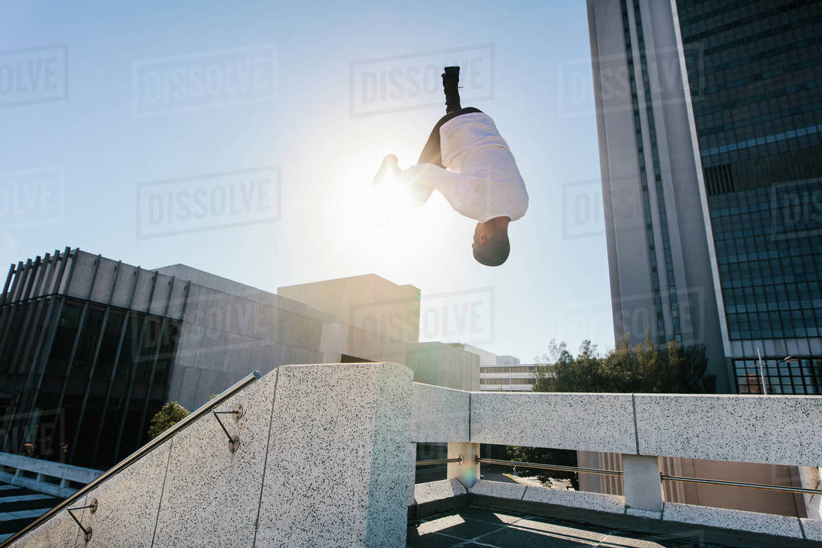 Man practices parkour and free running by doing a frontflip from a obstacle outdoors. Young man practicing extreme sport outdoors in city. Royalty-free stock photo