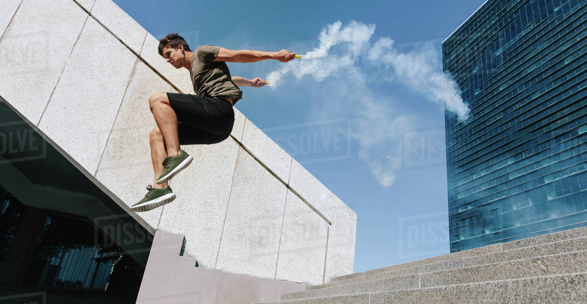 Free runner jumping over obstacle with smoke grenades  Young man doing  parkour stunts outdoors in the city  stock photo