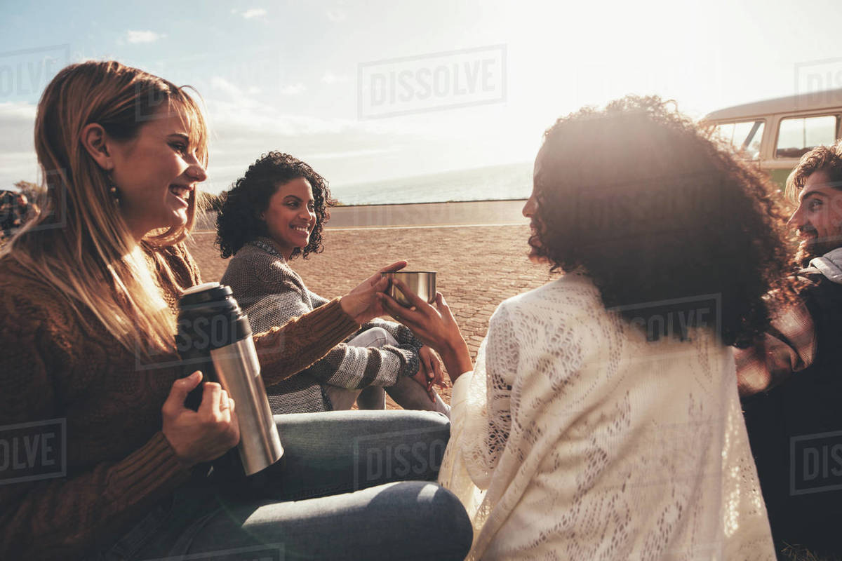 Friends On Roadtrip Taking A Break After Traveling Group Of Man And Women Sitting Outdoors And Drinking Coffee Stock Photo Dissolve