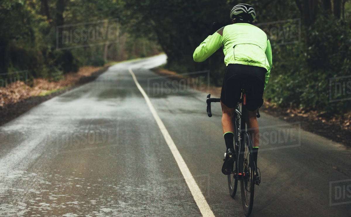 Rear view of male athlete cycling on country road on rainy day. Professional cyclist riding a bike on empty highway through forest. Royalty-free stock photo